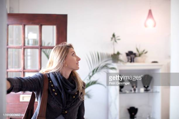 a small business owner turning on the lights in her shop. - turning on or off stock pictures, royalty-free photos & images