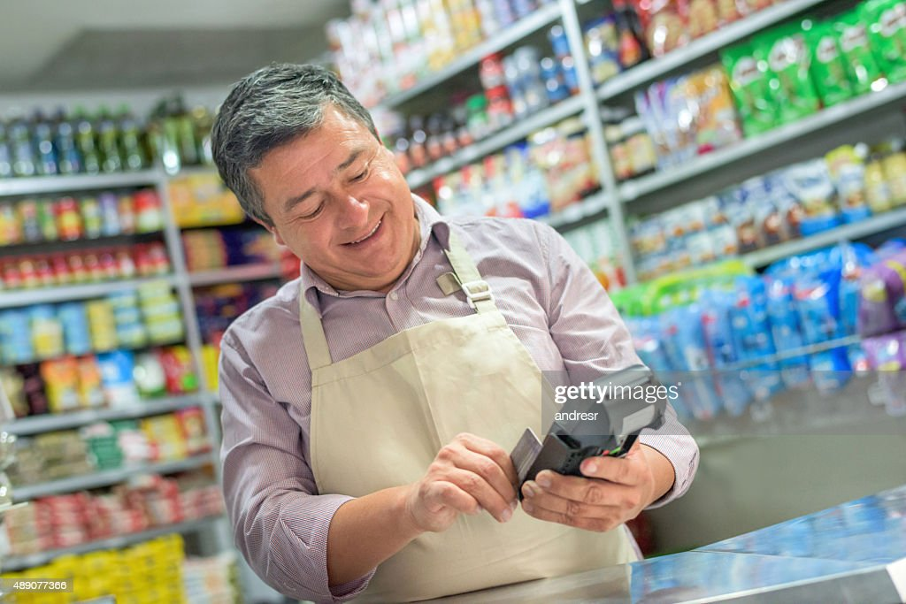 Small business owner using a credit card reader : Stock Photo