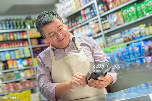 small business owner using a credit card reader - convenience store stock photos and pictures