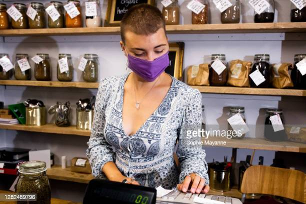 a small business owner working behind the counter in a refill shop - sustainable resources stock pictures, royalty-free photos & images