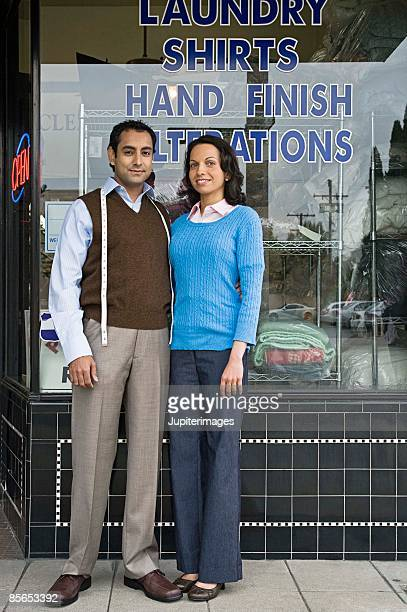 Small business owners in front of dry cleaners shop