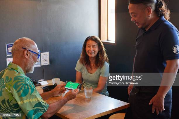 small business owners make contactless payments - chigasaki stock pictures, royalty-free photos & images