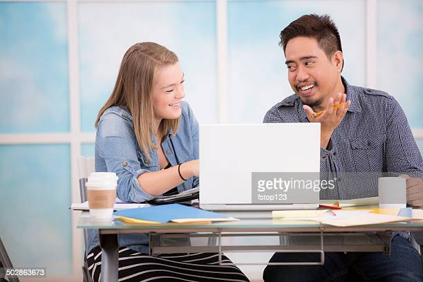 Small business, start up. Creative young adult co-workers collaborate. Laptop..