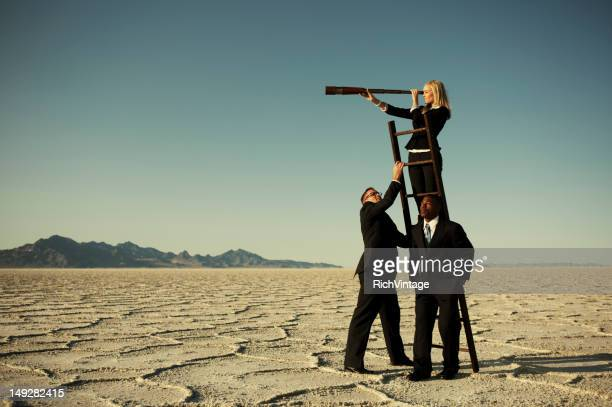 small business team search through telescope on salt flats - long hair stock pictures, royalty-free photos & images