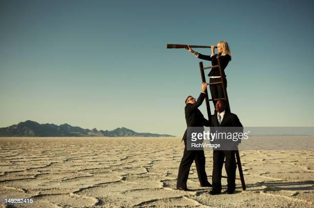 small business team search through telescope on salt flats - lang haar stockfoto's en -beelden