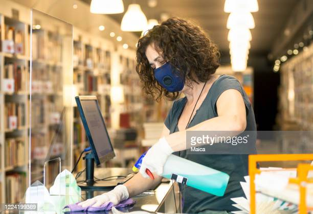 small business woman owner disinfecting pexiglass wall - disinfection stock pictures, royalty-free photos & images