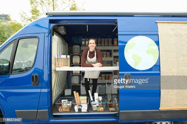 Small business woman working in zero waste wholefoods and local produce van.