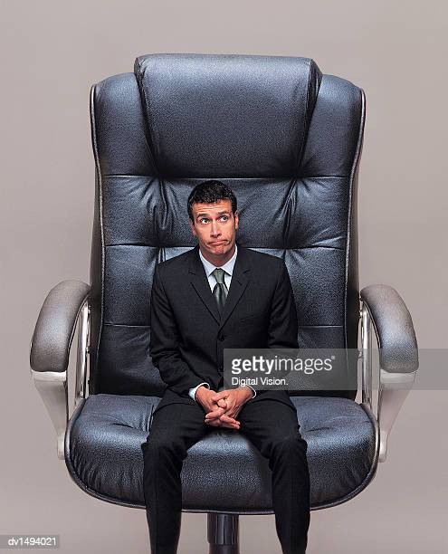 Small Businessman Sitting in a Big Office Chair