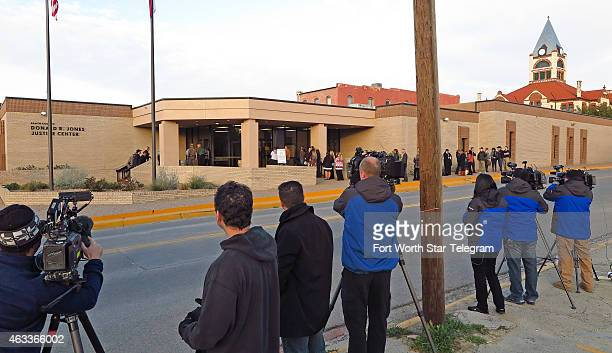A small but growing line of trial spectators watched by television crews wait to enter the Erath County Donald R Jones Justice Center in Stephenville...