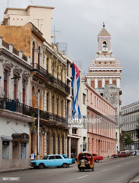 A small cab rides down the street in Havana Cuba Barcardi Rum Building is the tall building in the background