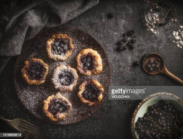 Small cakes on wooden plate with a black currant and jam