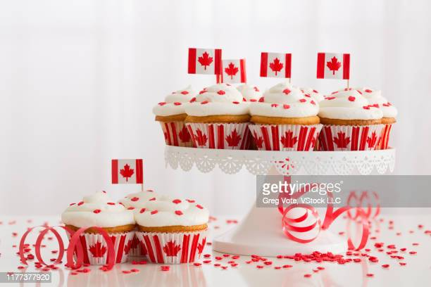 small canadian flags on red and white cupcakes - canada day stock pictures, royalty-free photos & images