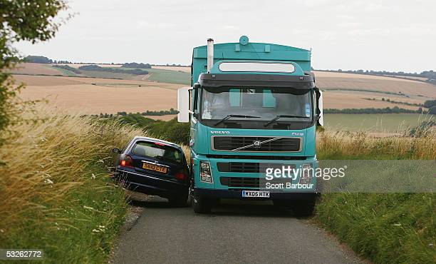 A small car and a large truck have difficulty passing each other on a narrow country road on July 19 2005 south of Salisbury England The future shape...