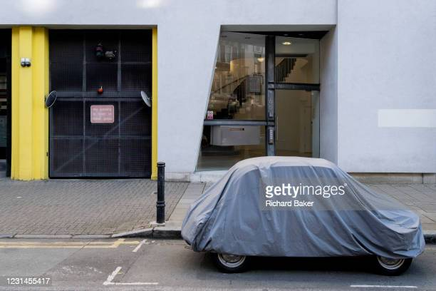 Small car is protected by plastic covering while parked on St John Street in Clerkenwell on 26th February 2021, in London, England.