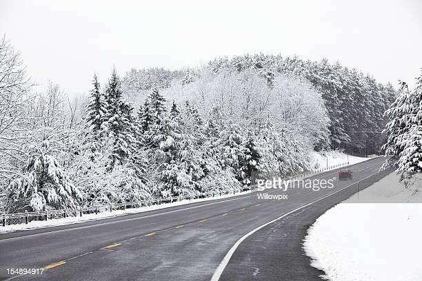 Small Car Speeding on Rural Adirondacks Highway in Blizzard