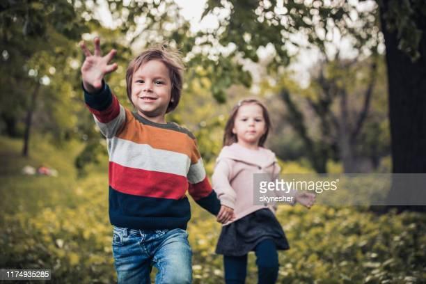 kleines unbeschwertes paar, das spaß beim laufen im park hat. - winken stock-fotos und bilder