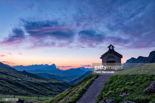 Small chapel close to Pordoi pass, Passo Pordoi at sunrise, the Setsas mountains in the distance.