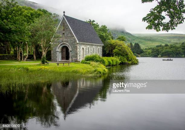 A small chapel sits peacefully on a lake in Ireland as a boat paddles by.