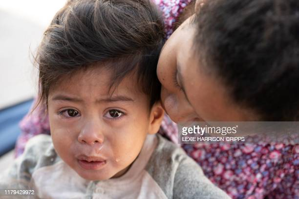 A small child cries in distress as his mother comforts him in the Matamoros camp in Matamoros Tamaulipas state Mexico near to the border with the...