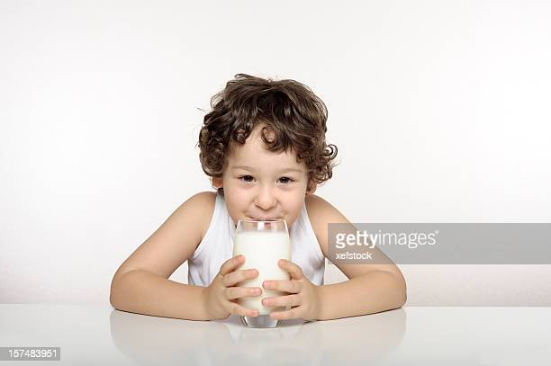 Small child drinking a glass of milk