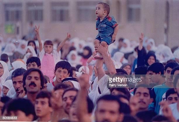 Small child held above veed finger-raising crowd at gulf crisis pro-Iraqi, anti-US rally organized by Muslim Brotherhood.