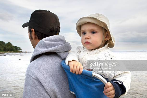 Small child in a baby carrier on her father«s back, Sweden.