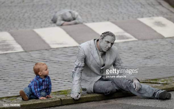 A small child looks at an actor covered in loam who takes part at the '1000 Figures' art action in Hamburg Germany 5 July 2017 The art action is part...