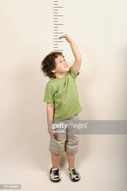 Small child measuring himself standing up