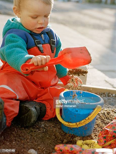 A small child playing in a sandpit.
