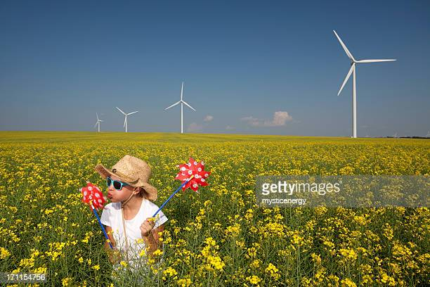 Small child playing in wildflower field with wind turbines