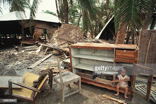 A small child sits inside a broken cabinet amongst the wreckage of a village devastated by one of the biggest cyclones to hit Bangladesh in recent...