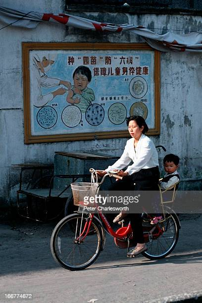 A small child sits on the back of a bicycle as her mother cycles past a healthcare poster on a wall The poster depicts a child being vaccinated by a...