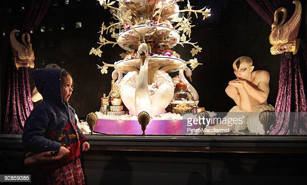 A small child watches as ballet dancers from Sadler's Wells Theatre pose in the newly unveiled Christmas window of Fortnum Mason grocery store on...