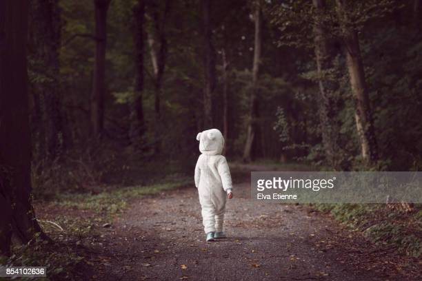 Small child wearing white bear suit, walking along a tree-lined forest path