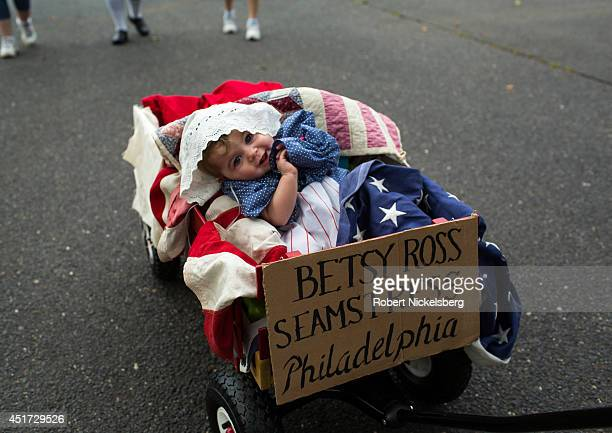 A small child wrapped in an American flag July 4 2014 is wheeled in the youth parade of the Independence Day celebrations in Ridgefield Park New...
