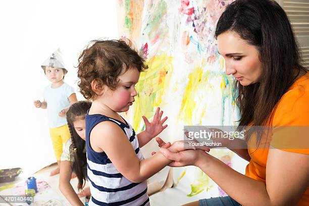 Small children draw paints on a paper wall