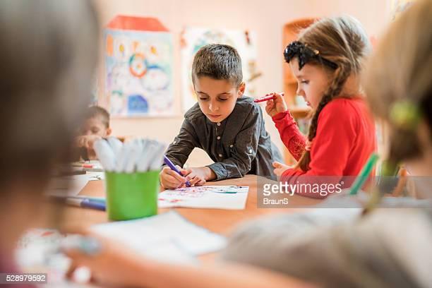 Petits enfants dessiner une classe de maternelle.