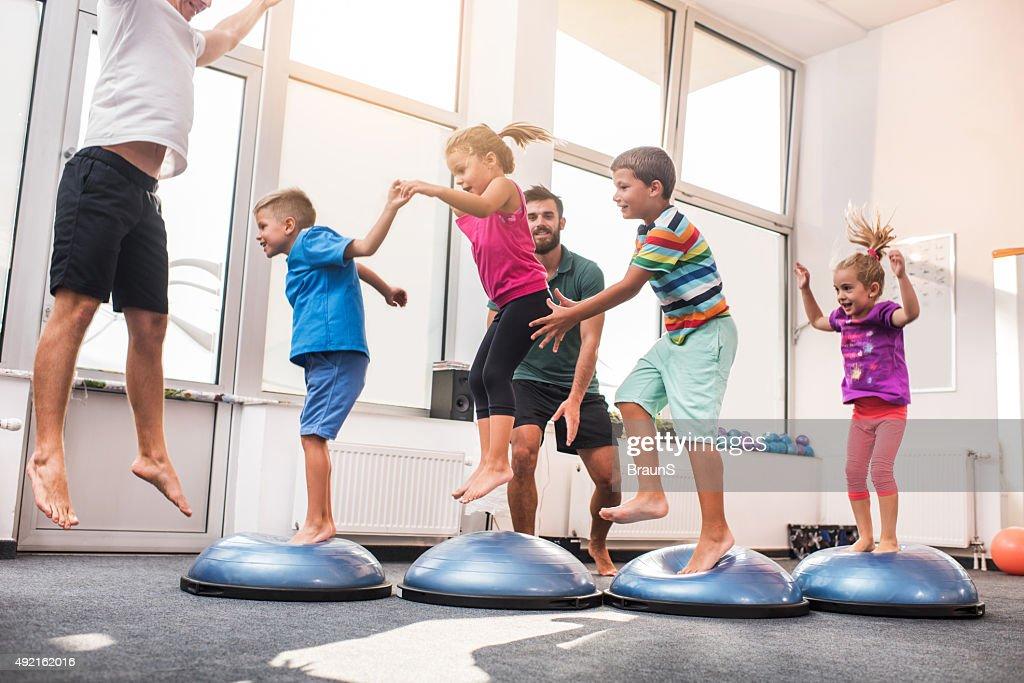 Small children jumping on bosu balls on training class. : Stock Photo