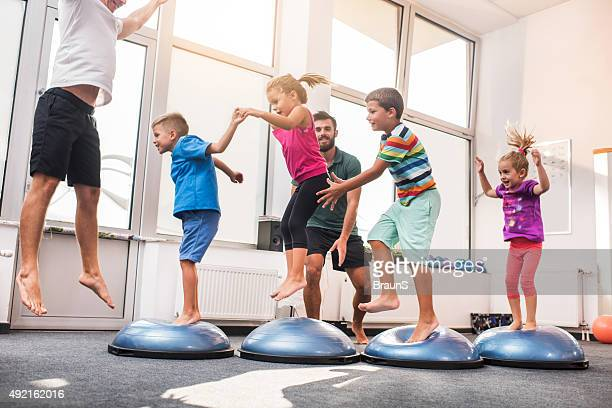 Small children jumping on bosu balls on training class.