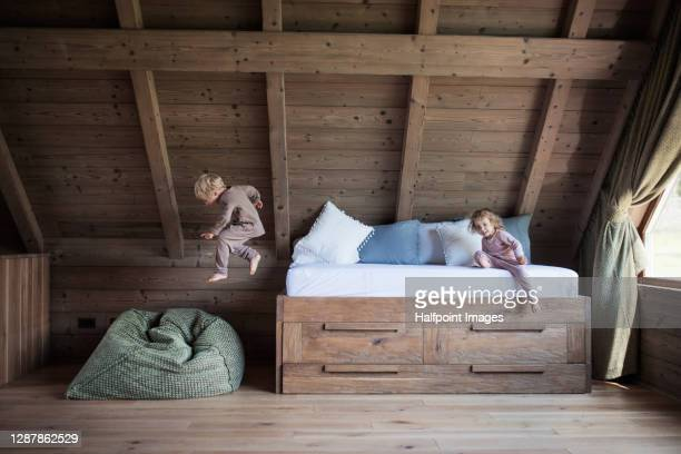 small children playing in bedroom on holiday, jumping from bed. - sacco photos et images de collection
