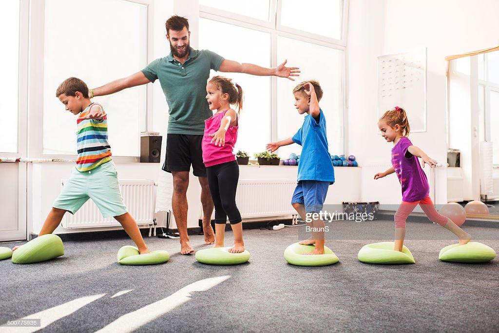 Small children walking on Pilates balls on training class. : Stock Photo