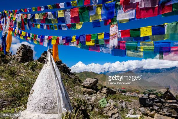 Small chorten stupas are located above town colorful buddhist prayer flags fluttering in the air the snow covered summit of Mt Dhaulagiri in the...