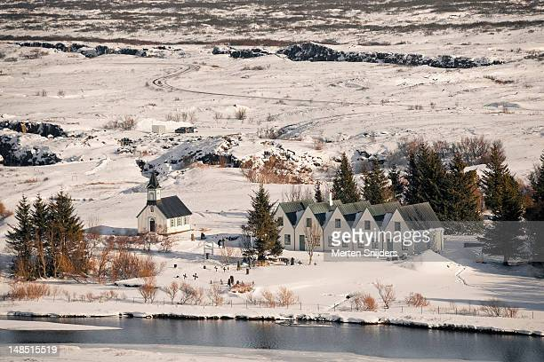 small church and houses in the thingvellir area, with wintry surrounding landscape. - merten snijders stockfoto's en -beelden