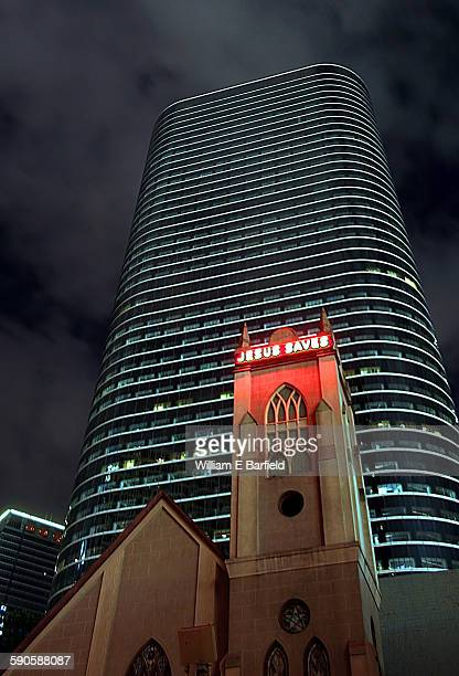 "Small church with red neon ""Jesus Saves"" sign shining at night with the former Enron building skyscraper looming in the background in downtown..."