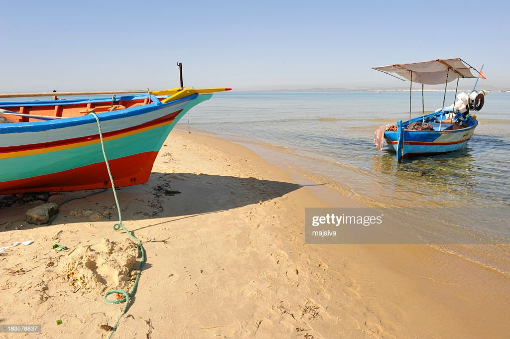 Small colorful fishing boats on shore and beach sand : Stock Photo