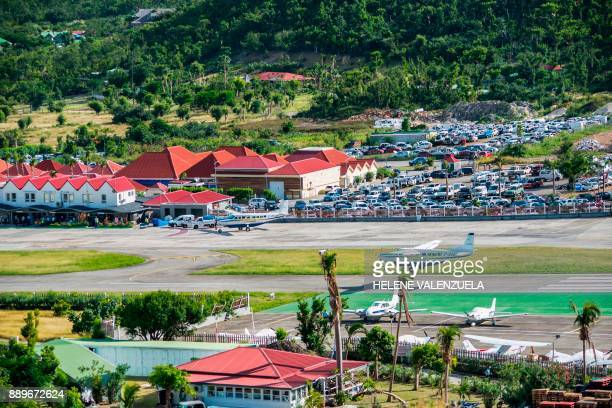 A small commuter plane lands at the SaintJeanGustave III airport on the French Caribbean island of SaintBarthelemy on December 10 2017 French music...
