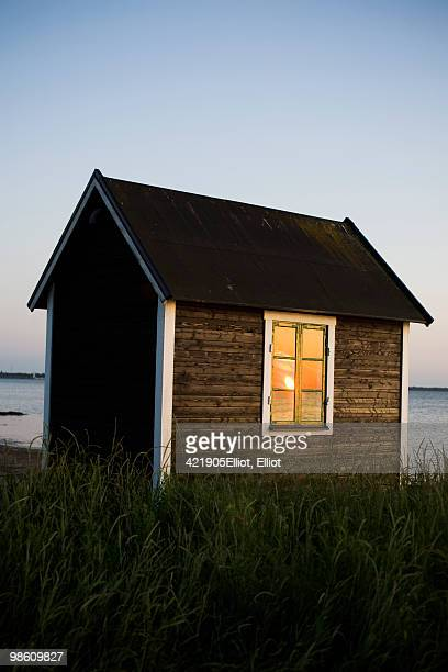A small cottage by the sea at sunset, Sweden.