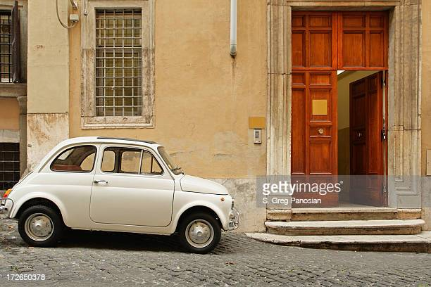 Small coupe parked near a doorway on a cobblestone street