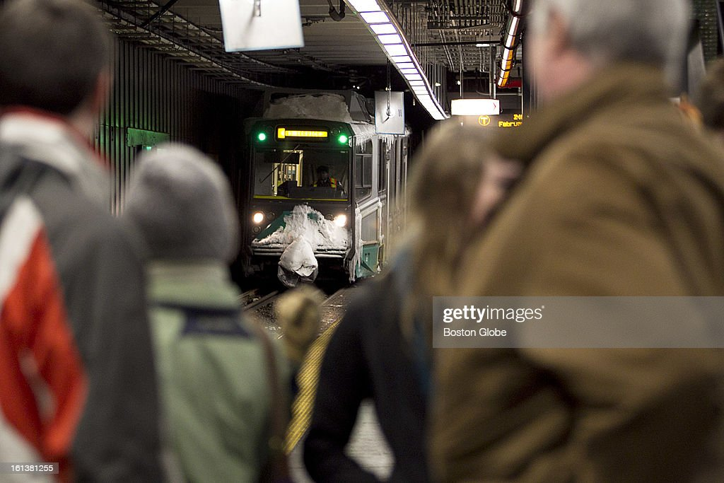 A small crowd watched as a green line T passed by, not stopping to pick up passengers. T riders wait for service to start on the green line at Kenmore Square in Boston, Mass. on Sunday, February 10, 2013. The MBTA announced it would resume limited service at 2 p.m.