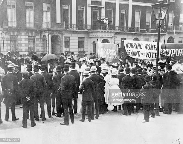 A small crowd watches the Women's Sunday procession as it passes Portland Place 21 June 1908 The protesters are almost at the end of their walk to...